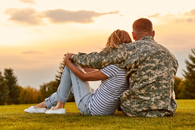 A soldier sitting with significant other watching the sunset.