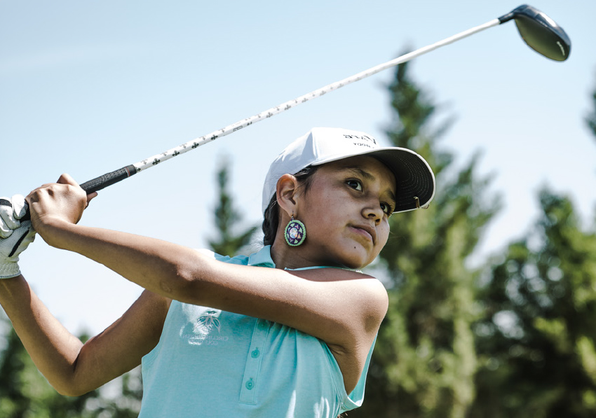 Young female golfer takes swing and looks forward.