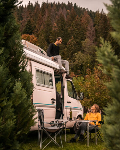Young couple enjoying holidays in a camper van, that bring the following advantages: ease of social distancing, connection with nature and digital detox. Picture taken in Romania.
